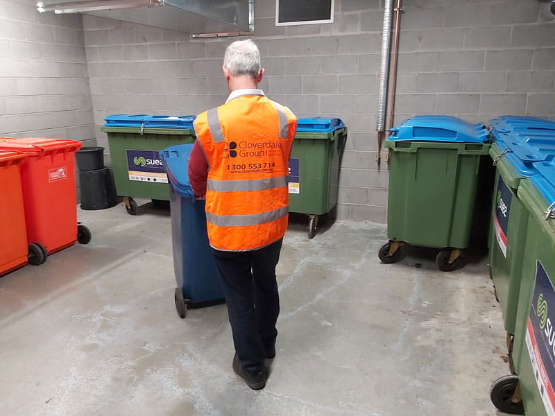 Caretaker pushing bins external