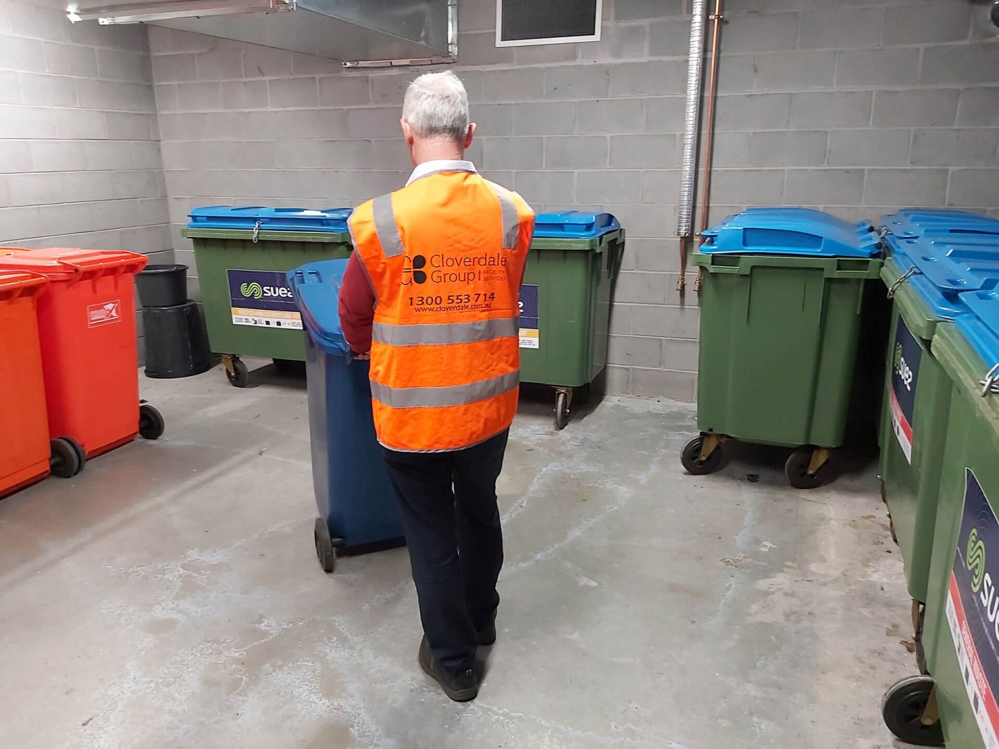 Caretaker pushing bins external corporate
